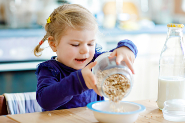 a young girl pours oatmeal into an empty white bowl at the kitchen table in her home