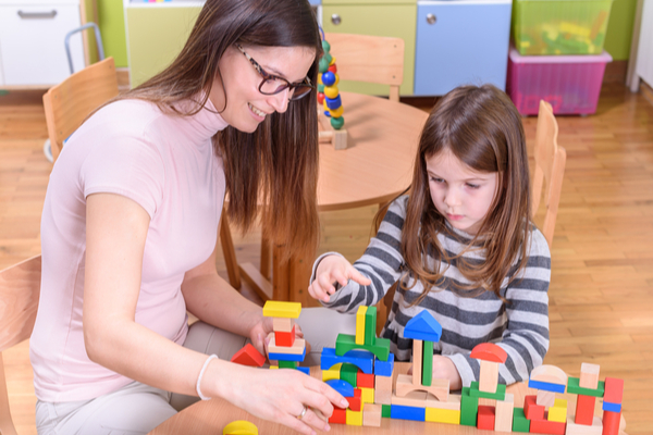 a young female childcare teacher with one of her students