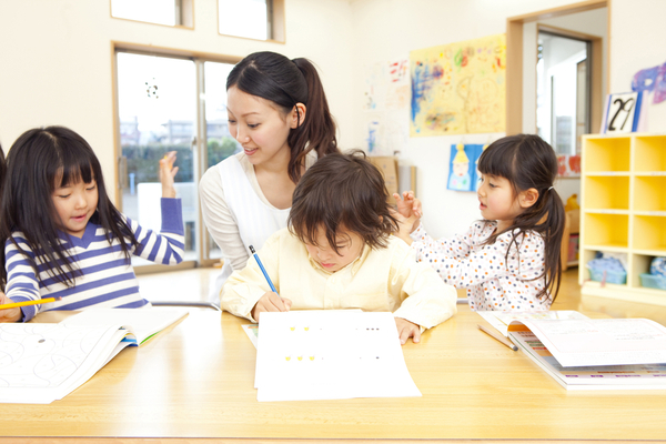 a work experience asian teacher doing simple writing tasks with her three students